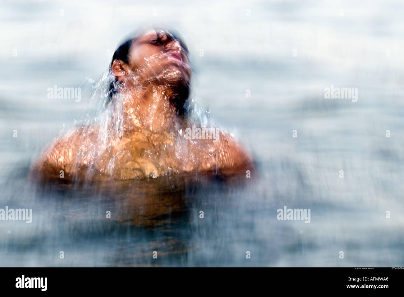 L'homme se baignant dans le Gange Varanasi Inde Photo Stock