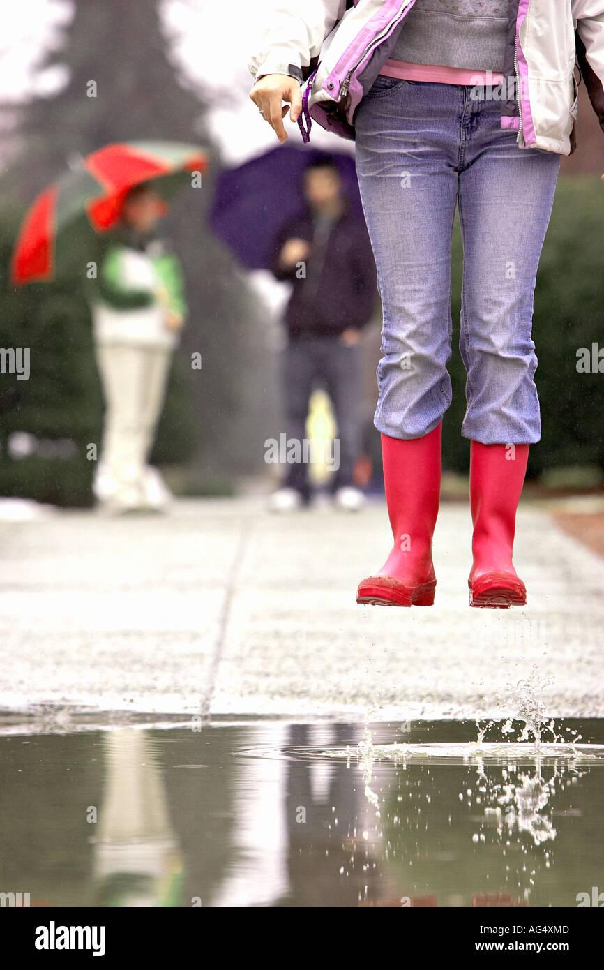 Jeune femme sauter dans une flaque d'eau avec des amis en arrière-plan l'exercice parapluies dans la pluie 12 29 ans 20 ans 20 s 20 30 Photo Stock