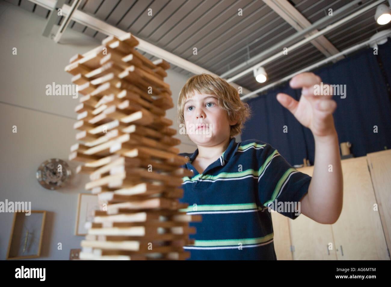 Garçon de huit ans l'empilement de blocs en bois aussi élevé qu'il peut regarder, de s'assurer Photo Stock