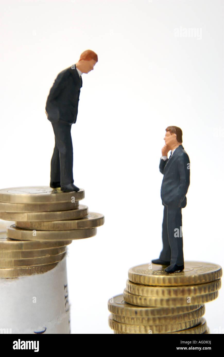 Entreprises / voyage / prêt / finances / prendre / investissement - deux figures debout sur des piles de pièces Photo Stock