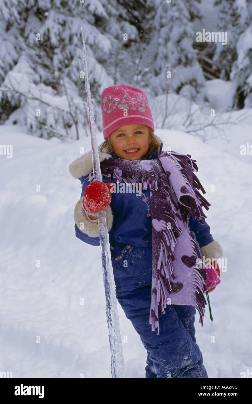 Jeune fille suce sur Icicle SC Hiver Alaska Banque D'Images