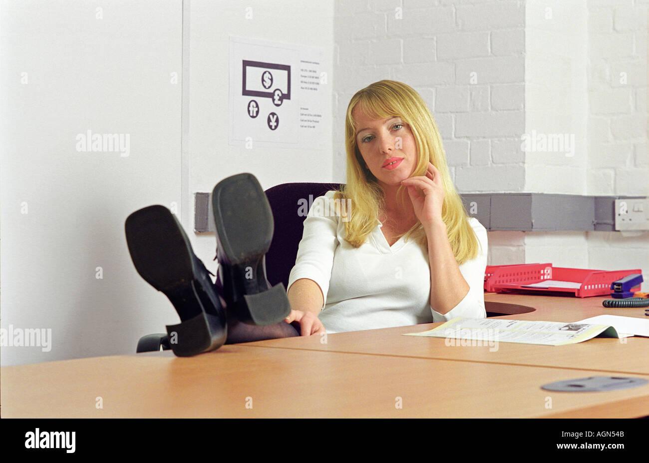 Le portrait de jeune femme d affaires dans un bureau avec pieds