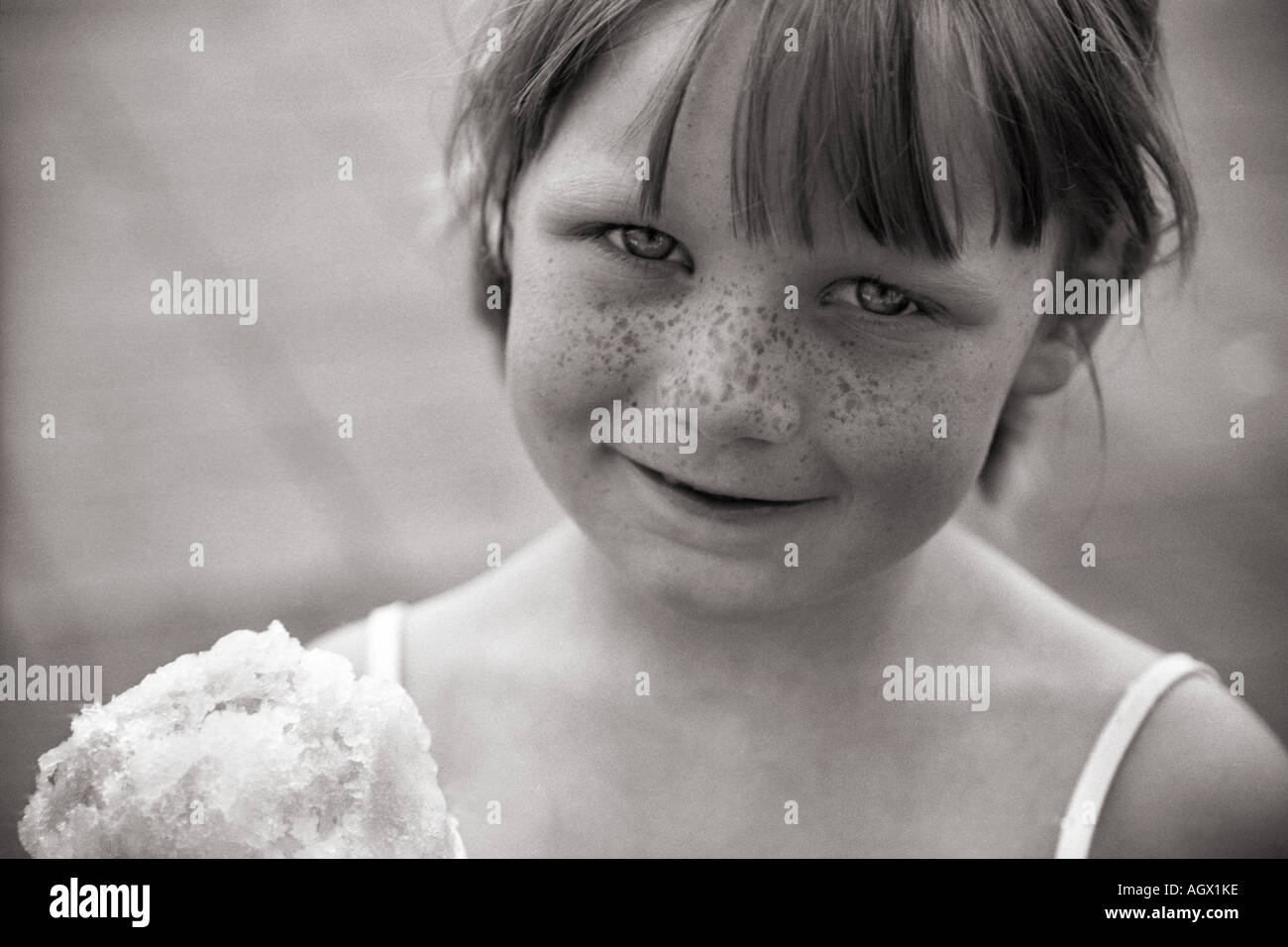 Gros plan d'une rousseur face fille avec cône de neige. Photo Stock