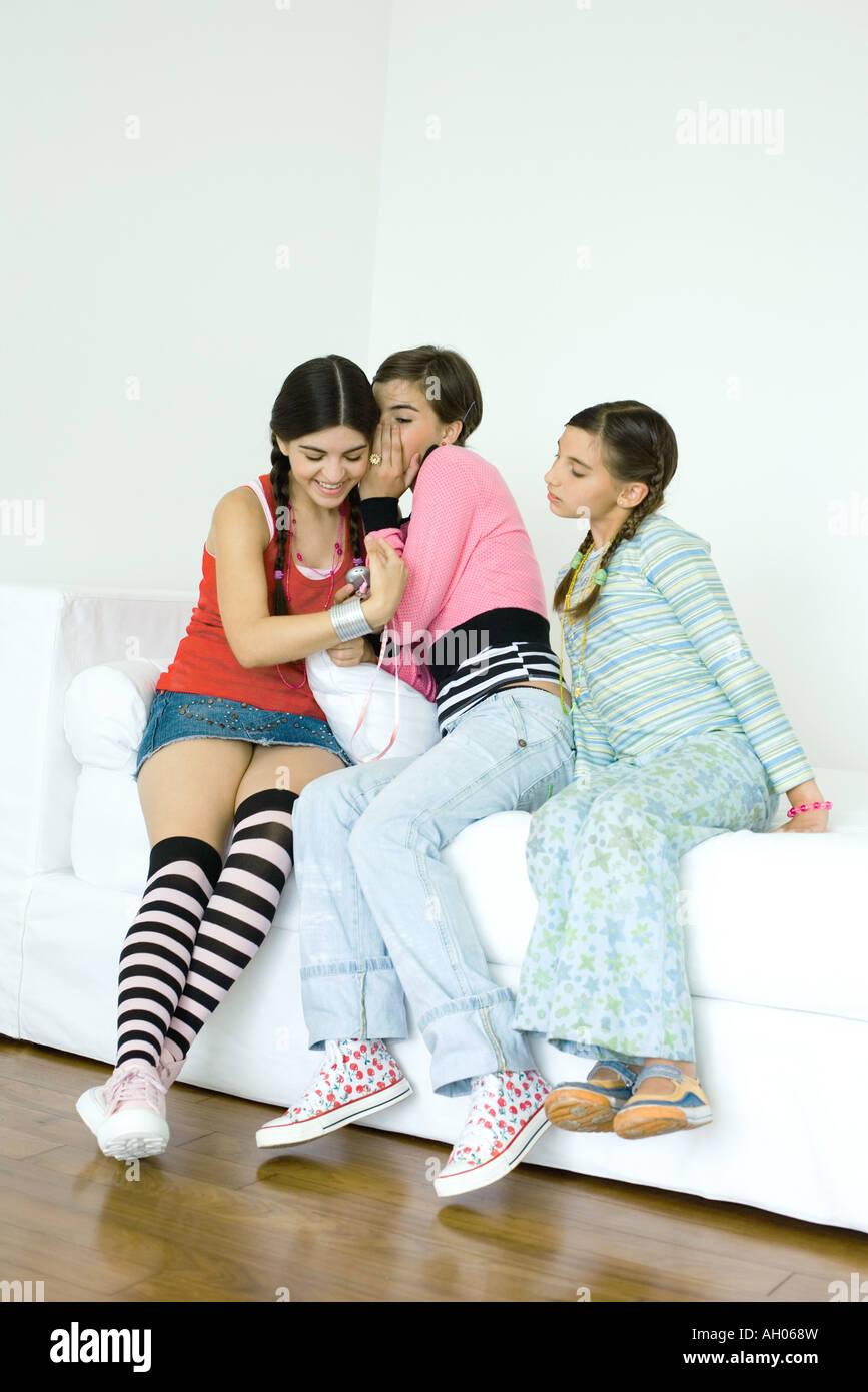 Trois jeunes amis féminins assis sur un canapé, un chuchotement à l'autre tout en troisième eavesdrops Banque D'Images