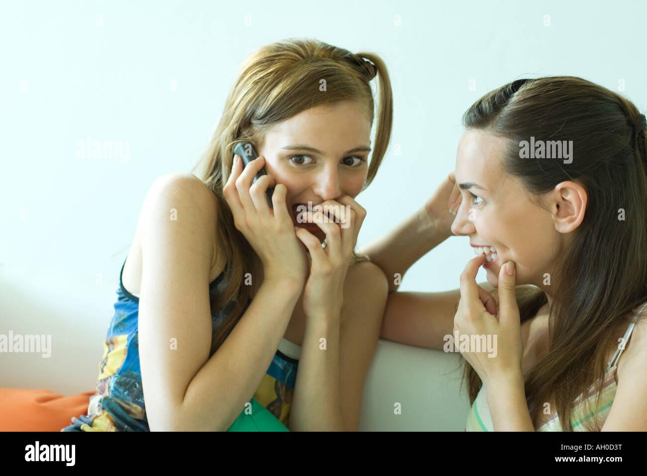 Deux jeunes amis siégeant ensemble, souriant, l'un à l'aide d'un téléphone cellulaire, Photo Stock