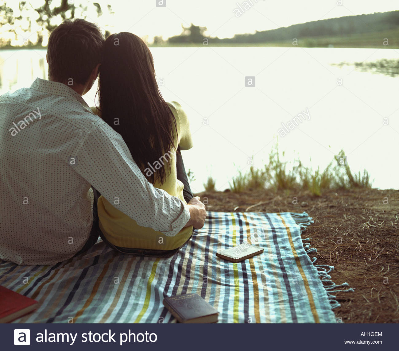Un couple relaxing by a lake Photo Stock