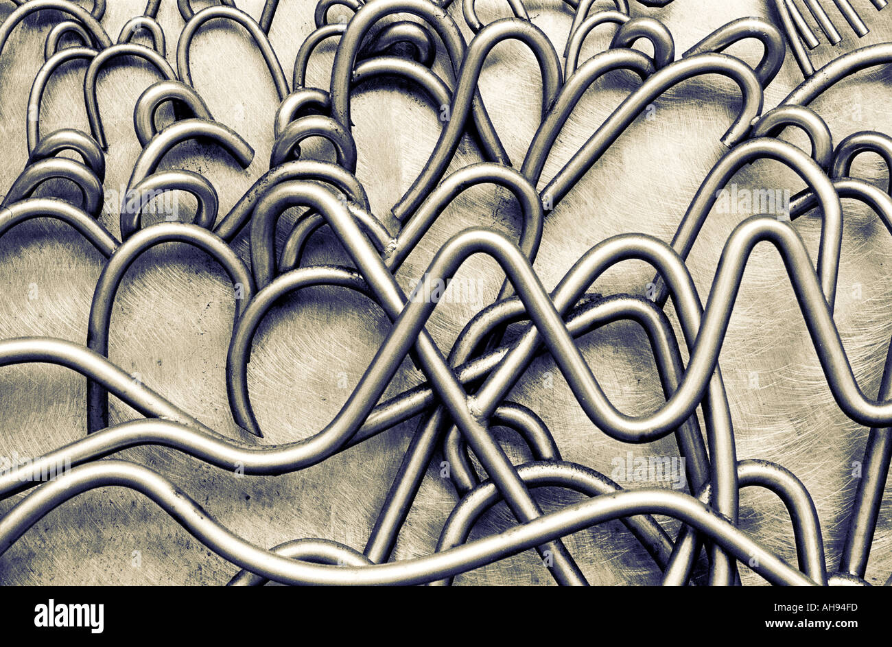 Twisted et tubes métalliques sculptées comme des câbles sur la surface de métal réfléchissant Photo Stock
