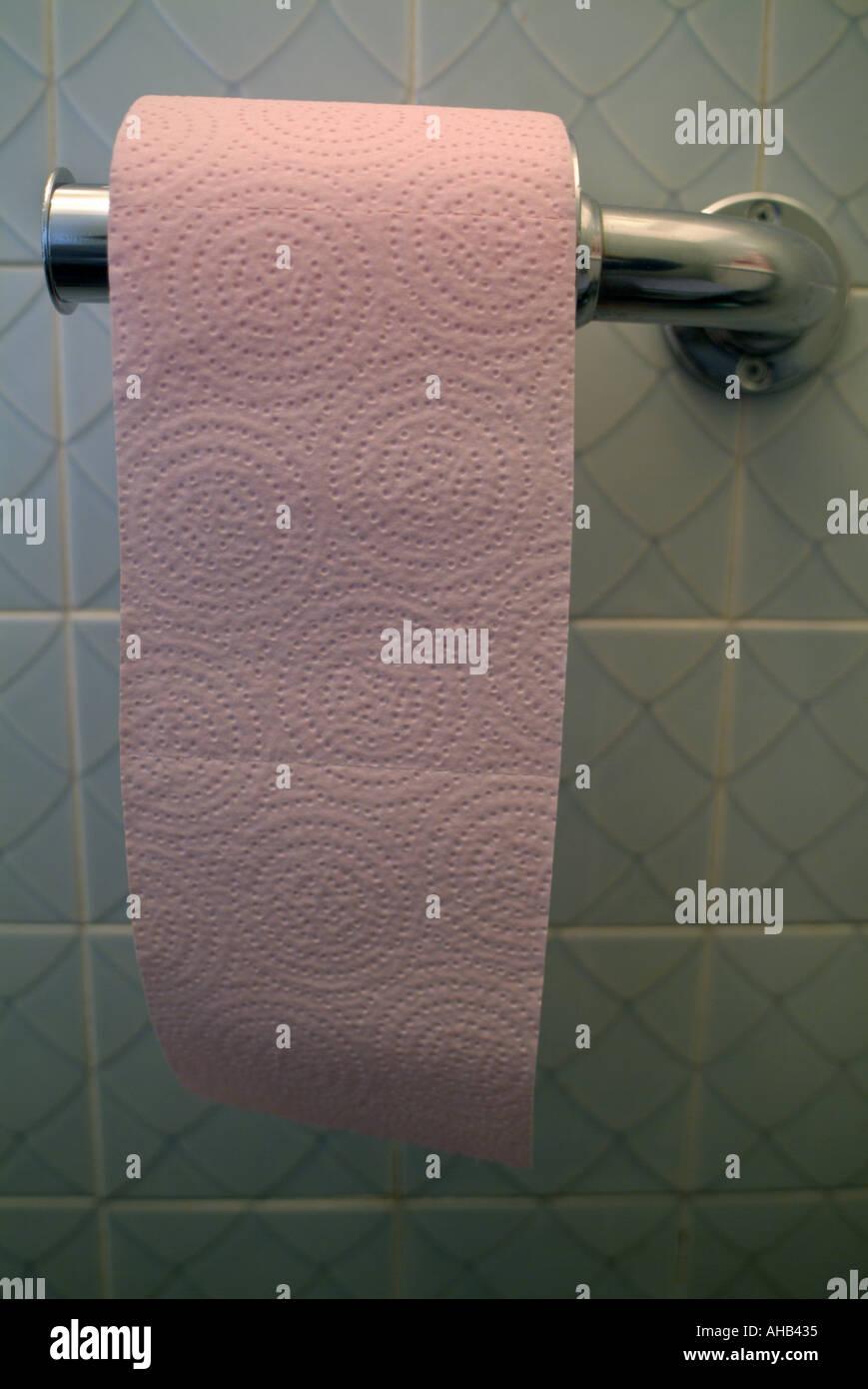 Rouleau de papier toilette rose dans la salle de bains. Photo Stock