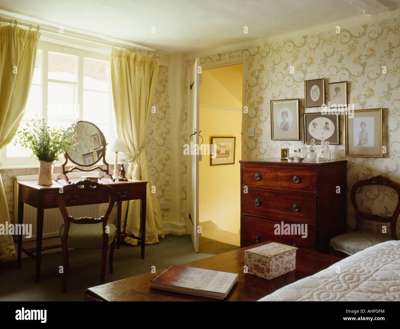 rideaux jaune pastel dans un chambre avec un papier peint motifs et neutre commode ancienne de tiroirs et une table de