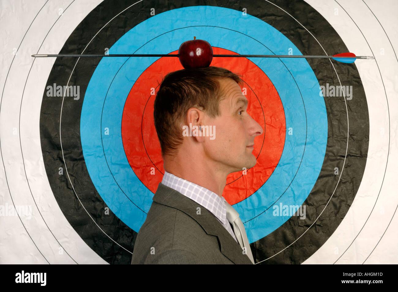 Businessman en face d'une cible avec une pomme et flèche sur la tête Photo Stock
