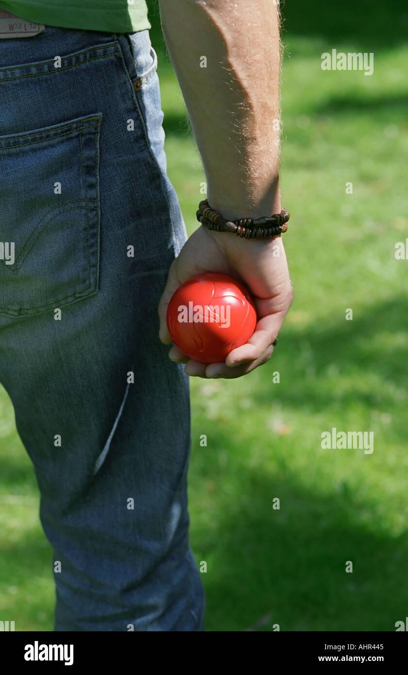 Homme tenant une boule rouge dans sa main. Banque D'Images