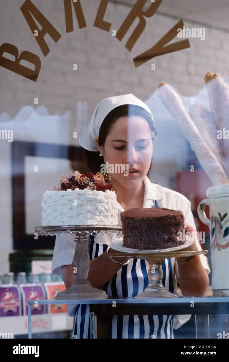 Caucasian propriétaire de petite entreprise en plaçant les produits de boulangerie dans la fenêtre de magasin de détail Photo Stock