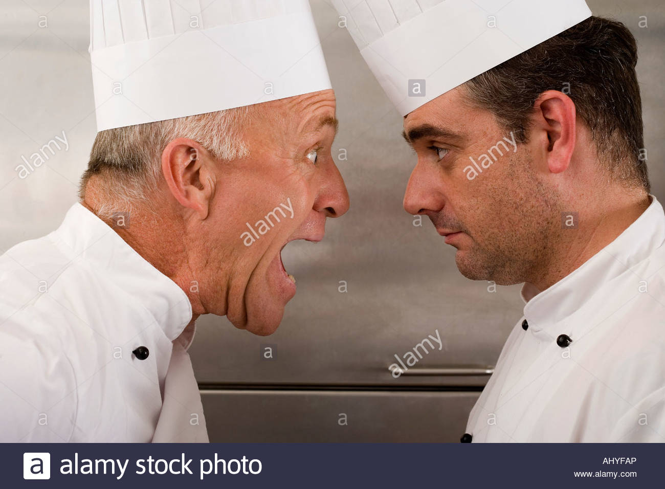 Angry senior chef de crier en chef junior cuisine commerciale face à face close up Photo Stock