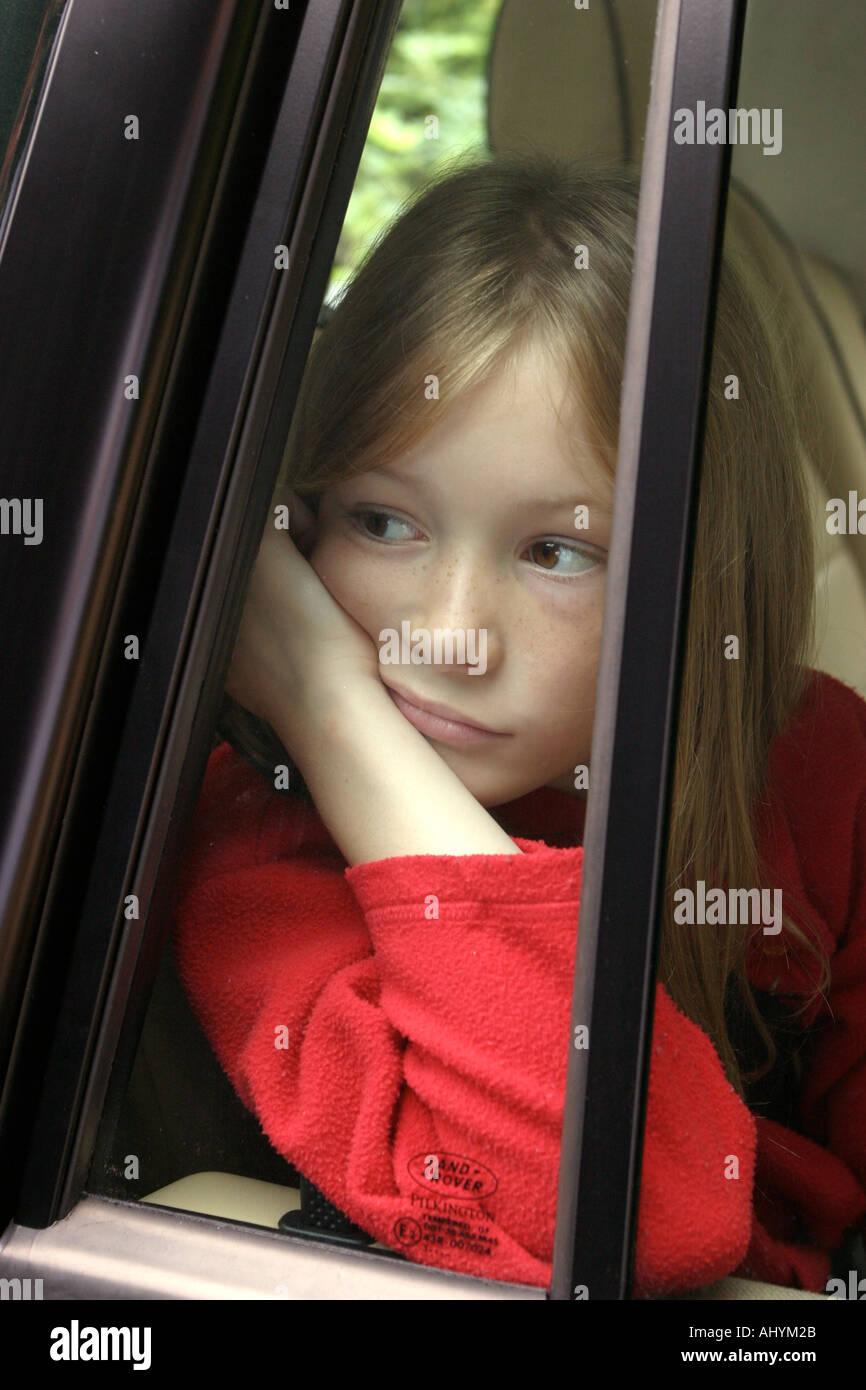 Ennuyeux, triste jeune passager voiture regarde hors de la fenêtre de voiture Photo Stock