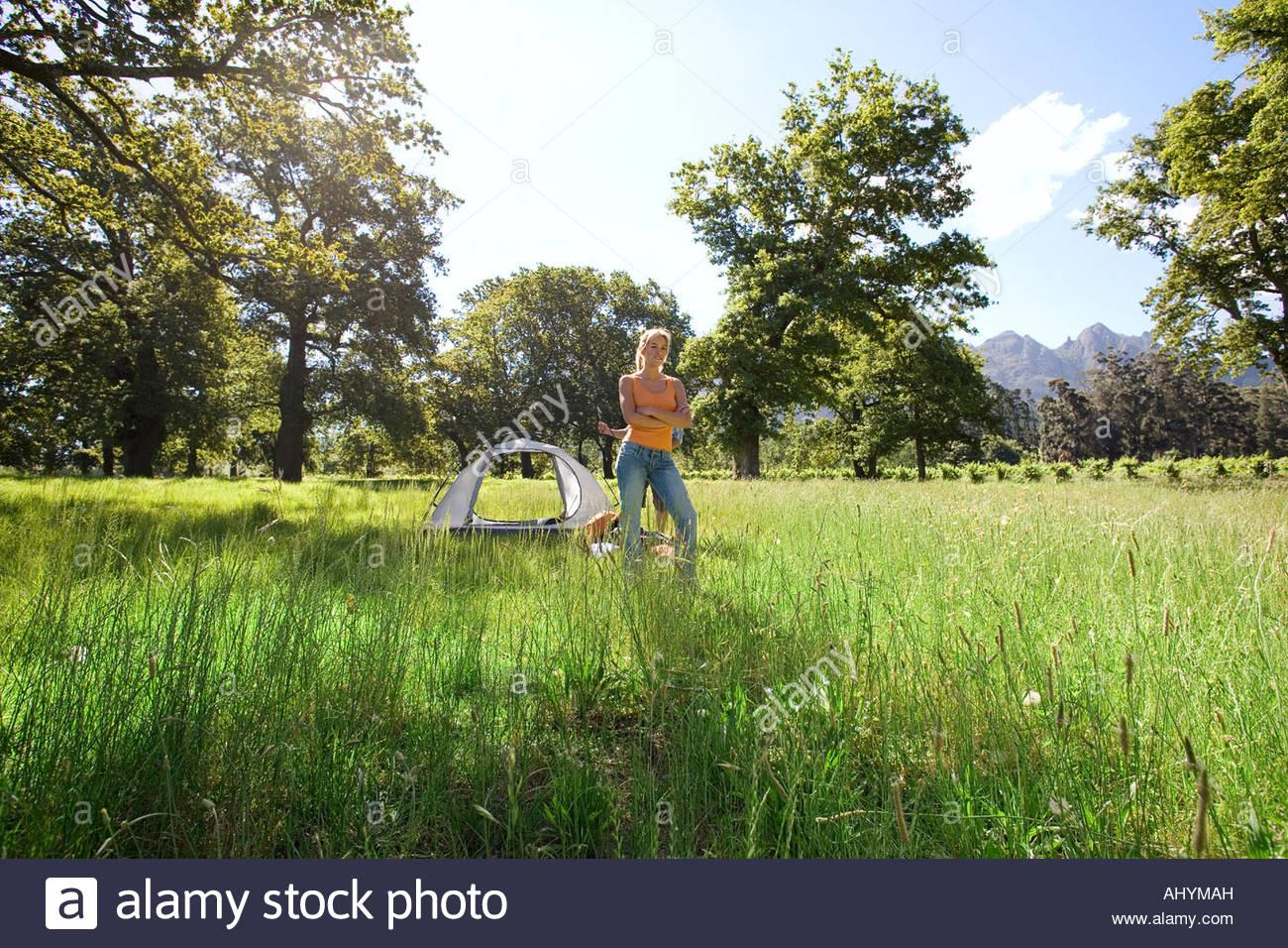 Jeune femme se tenir à la mi-distance près de tente dôme incomplète du camping dans le défrichement des terres forestières, Banque D'Images