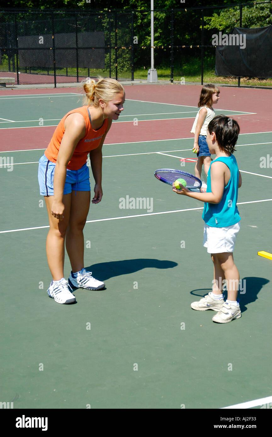 Les enfants apprennent à jouer au tennis à cour de récréation publique Photo Stock