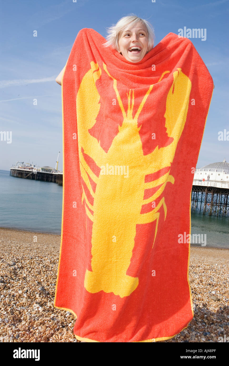 Jeune femme à la plage rouge tenant une serviette de plage qui un homard jaune imprimé sur elle Photo Stock