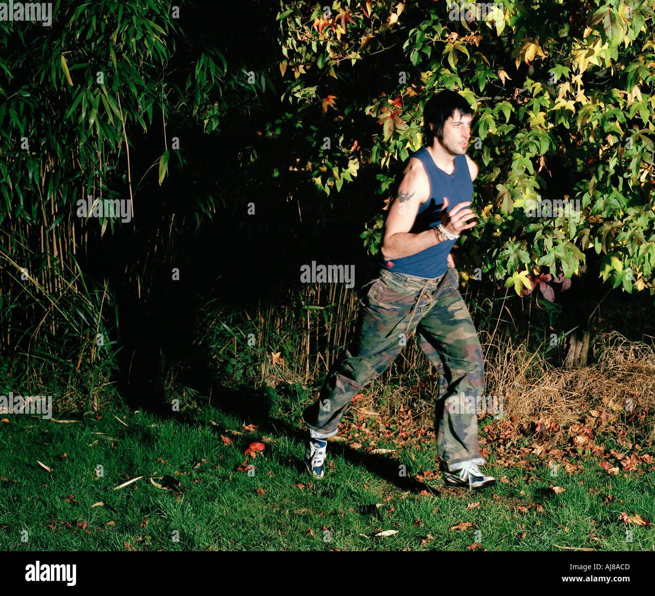 Homme qui court à travers les bois dans la nuit Photo Stock
