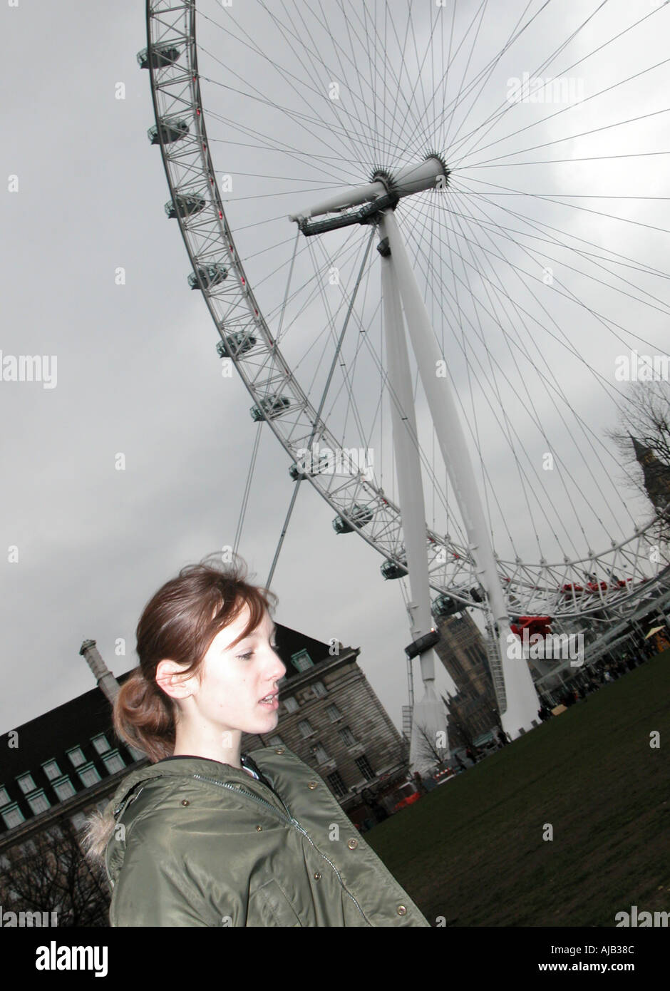 Teenage girl in parka en face du London Eye Banque D'Images