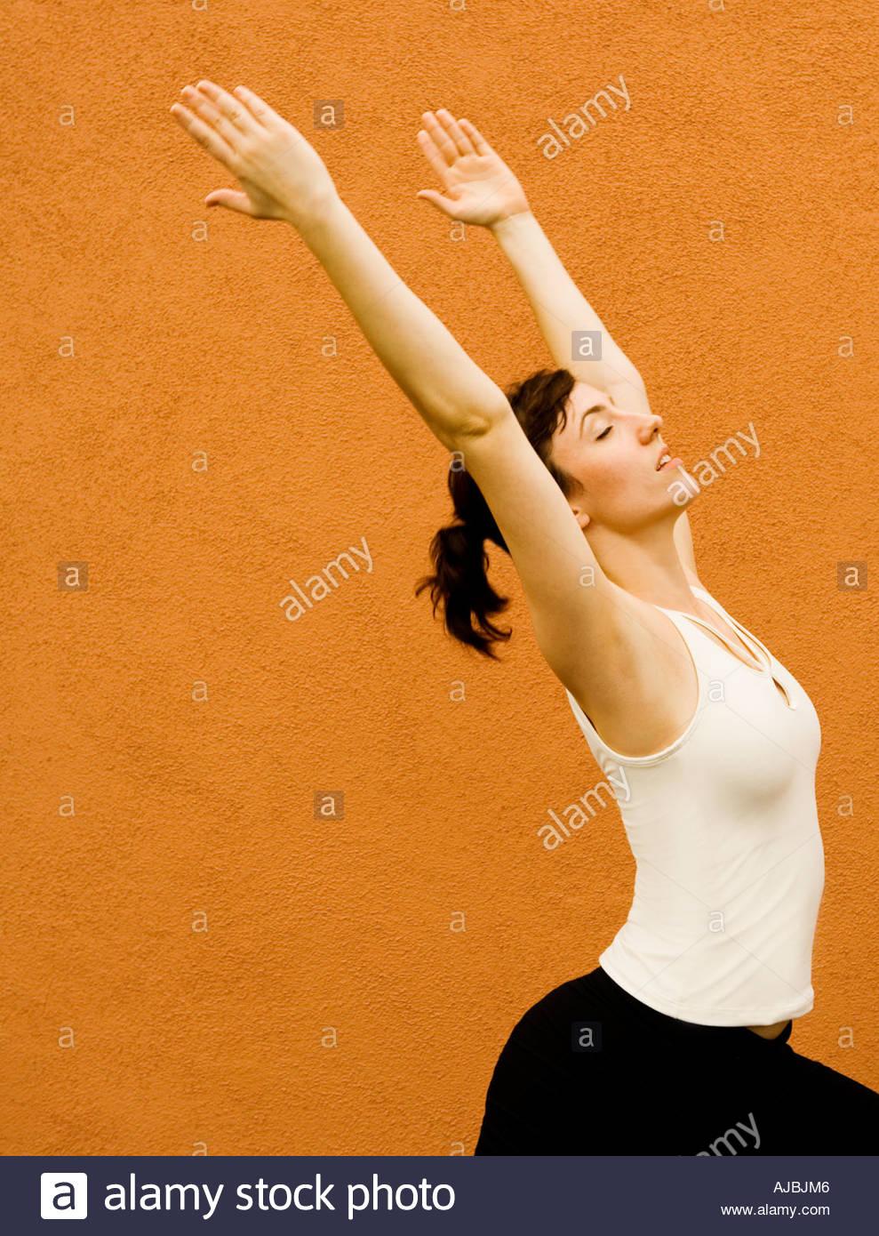 Femme adulte en Yoga comme étirer posent avec force la beauté de l'équilibre et la grâce en avant du mur de couleur terre cuite Photo Stock