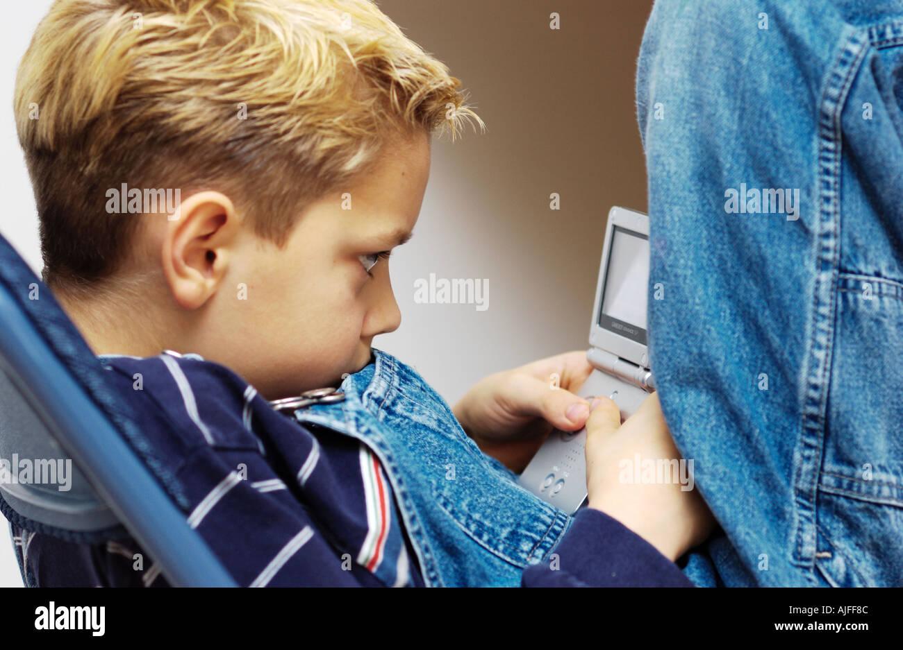 Jeune garçon se concentrant sur le jeu vidéo Photo Stock