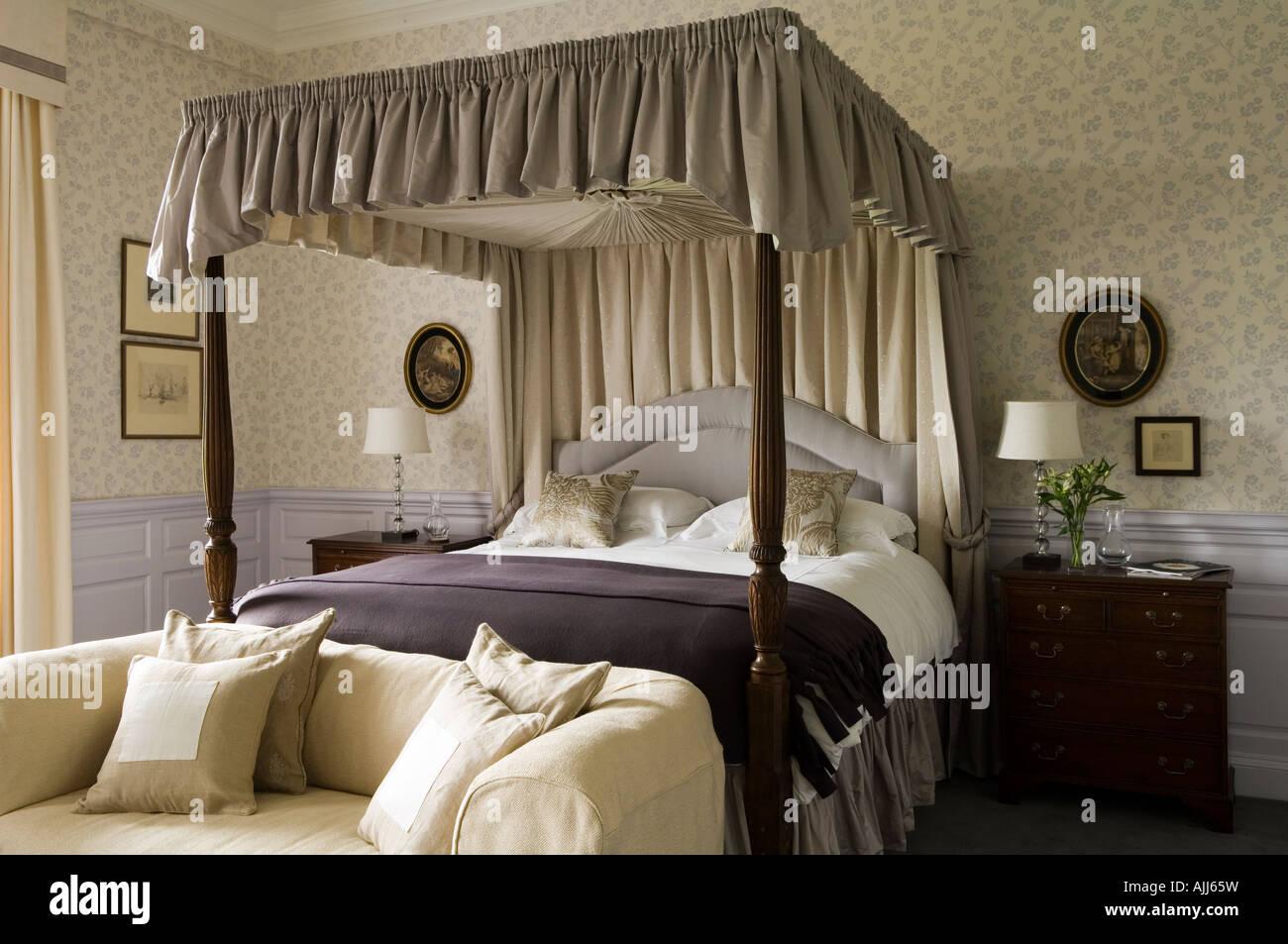 Lit à baldaquin et un canapé dans la chambre avec du papier peint à motifs violet au 17e siècle Photo Stock