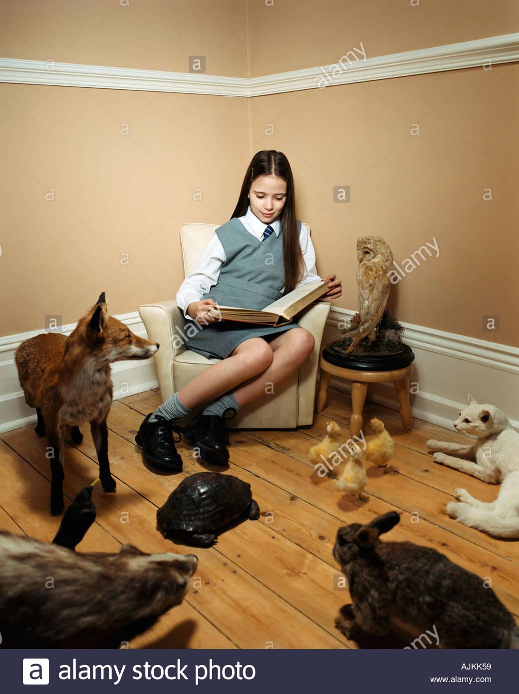 Girl reading histoire d'animaux en peluche Banque D'Images