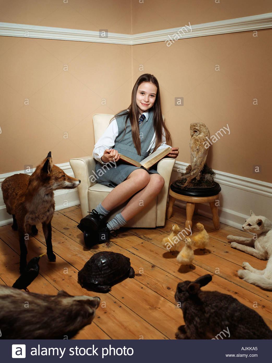 Girl reading histoire d'animaux en peluche Photo Stock
