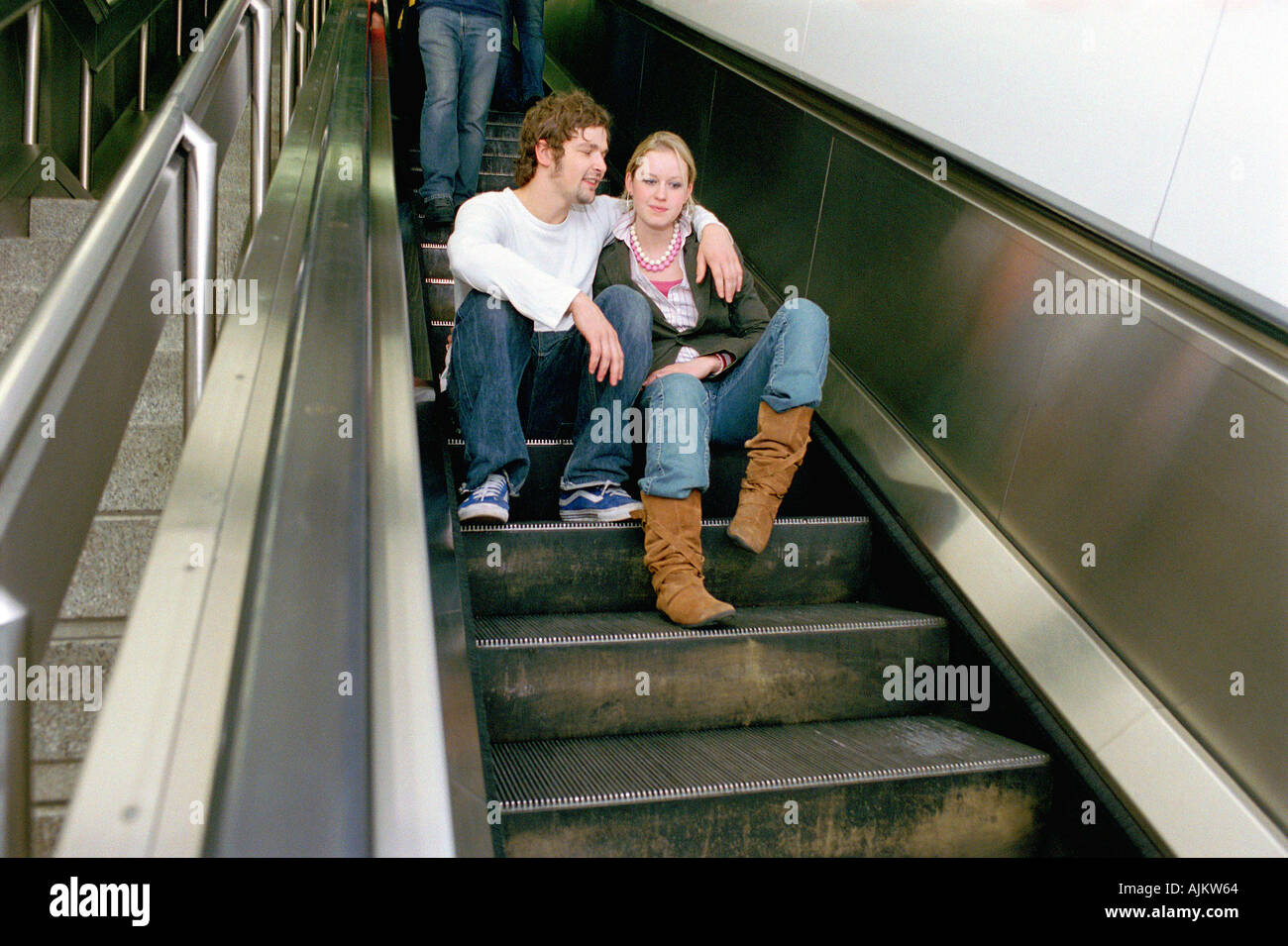 Couple sitting on escalator Banque D'Images
