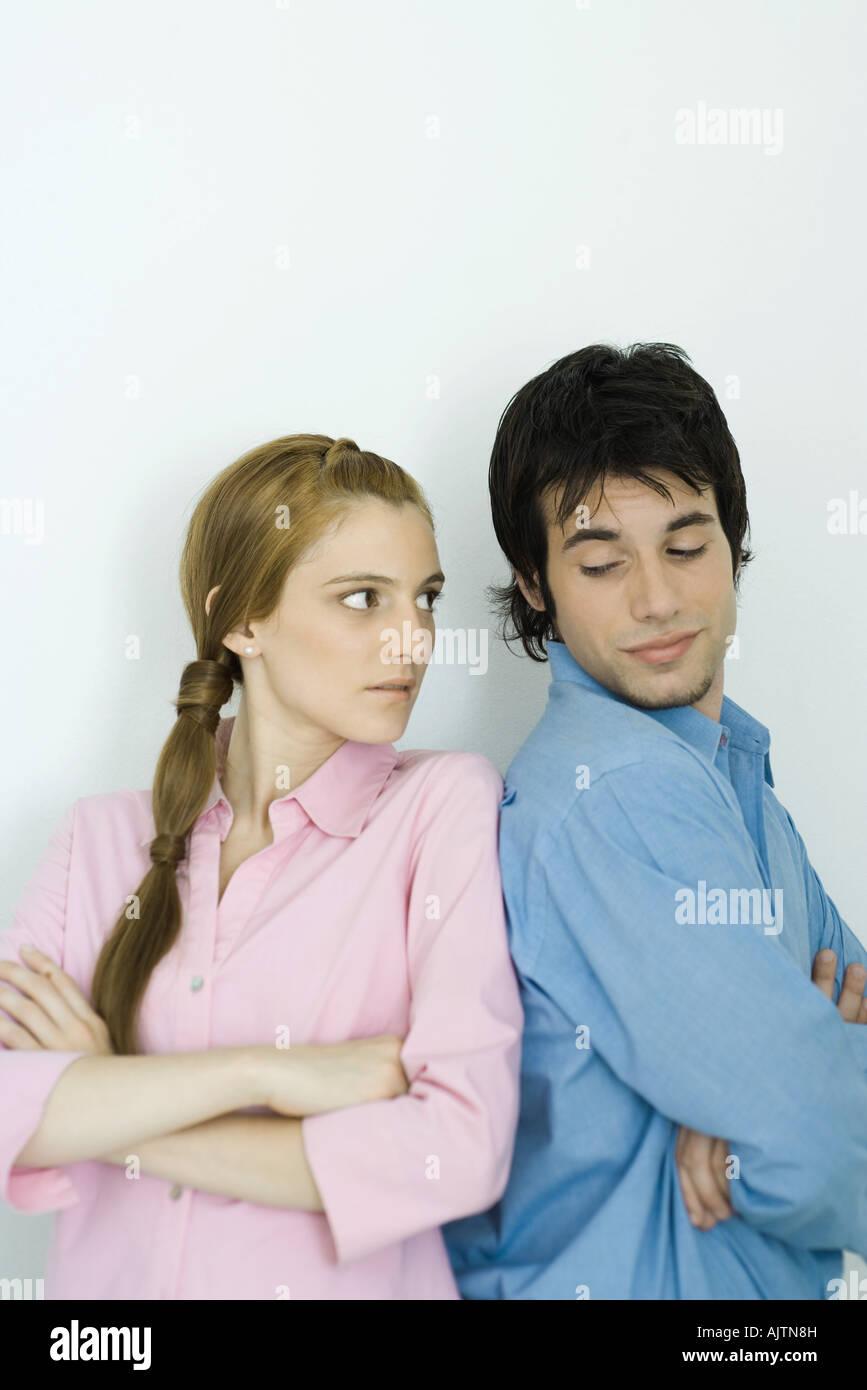Jeune couple sur leurs épaules, bras croisés Banque D'Images