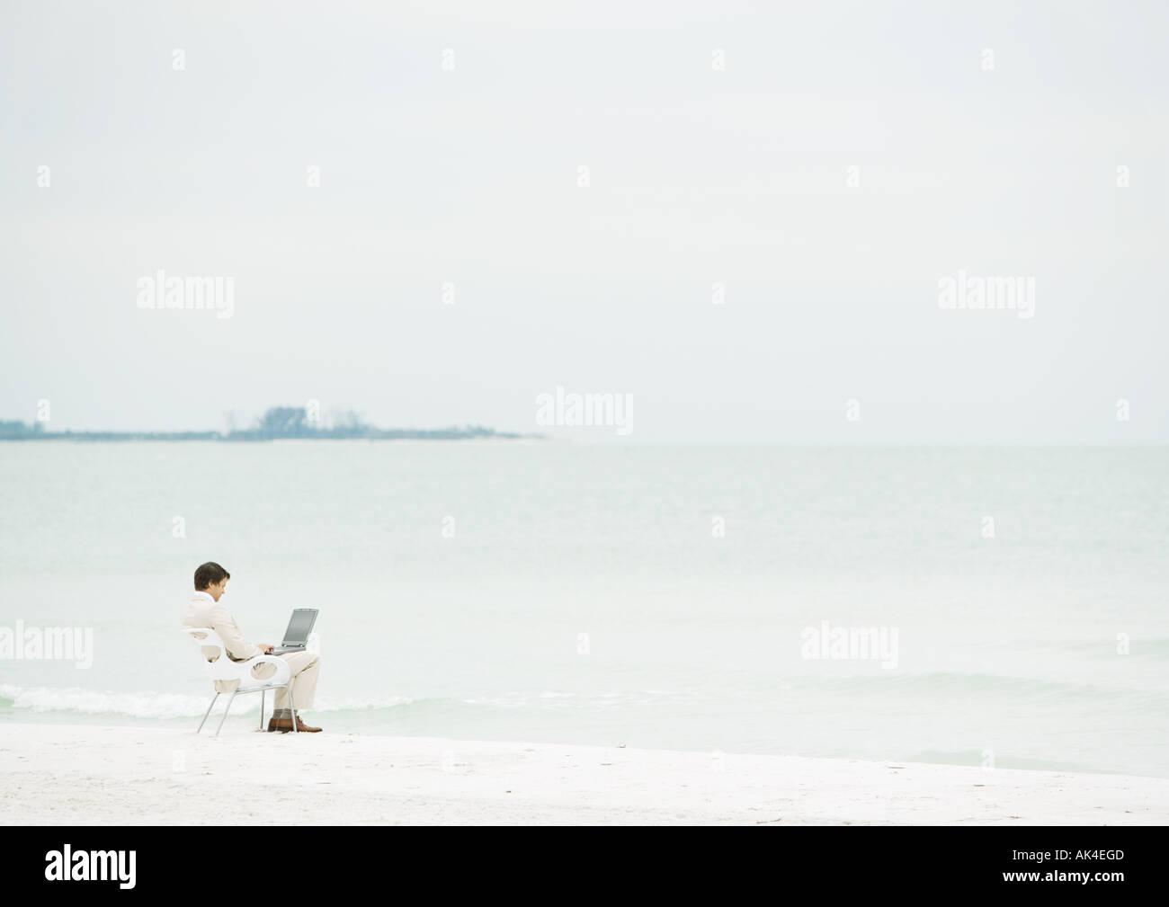 Businessman using laptop on beach, mi-distance Photo Stock
