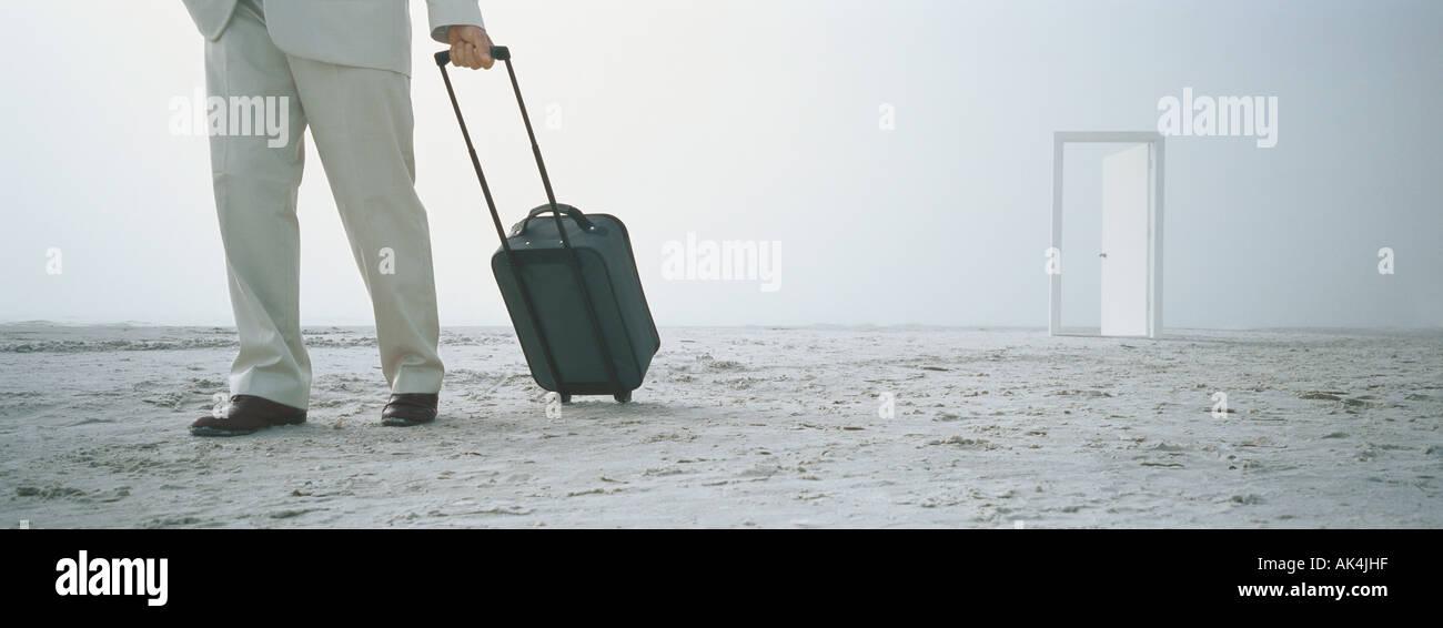 Businessman with suitcase on beach, porte en arrière-plan Photo Stock
