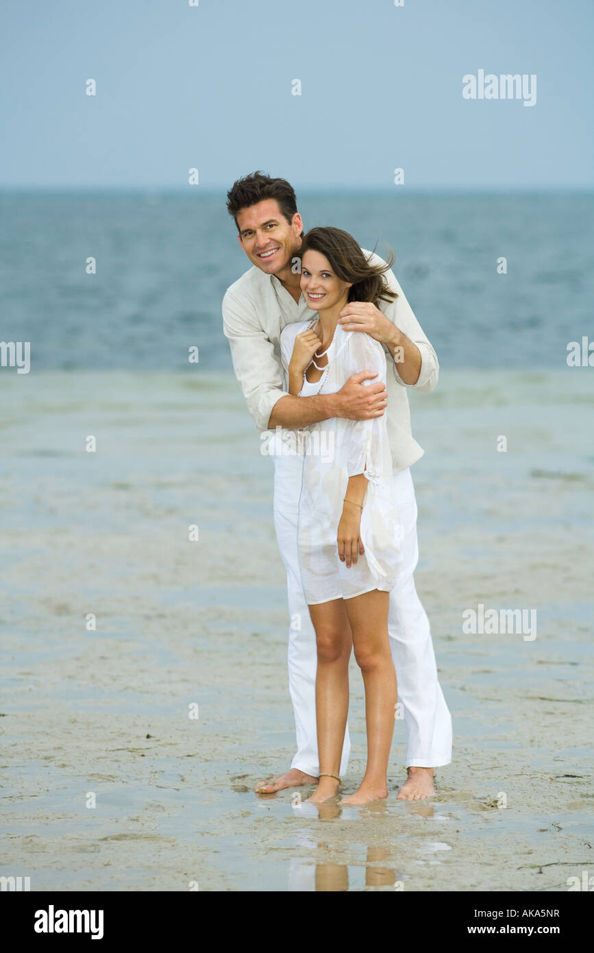 L'homme et la jeune compagne sur plage, Standing together, looking at camera, pleine longueur Photo Stock