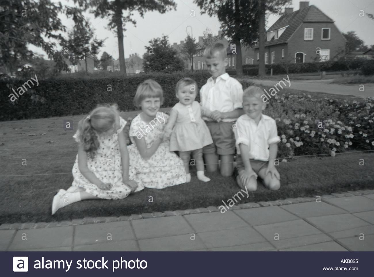 Filles et garçons posant pour une photo de famille 1960 s Photo Stock