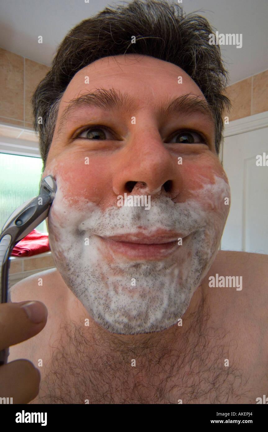 Fin des années 30 l'homme 30 ans de rasage humide avec de la mousse à raser sur le visage sur le point de raser Photo Stock