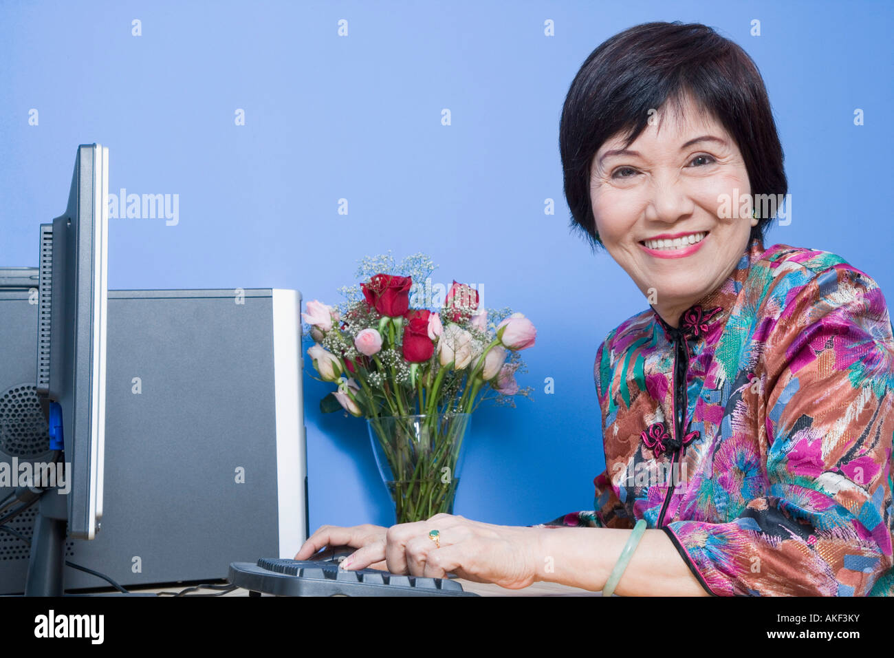 Portrait of a senior woman using a computer and smiling Banque D'Images