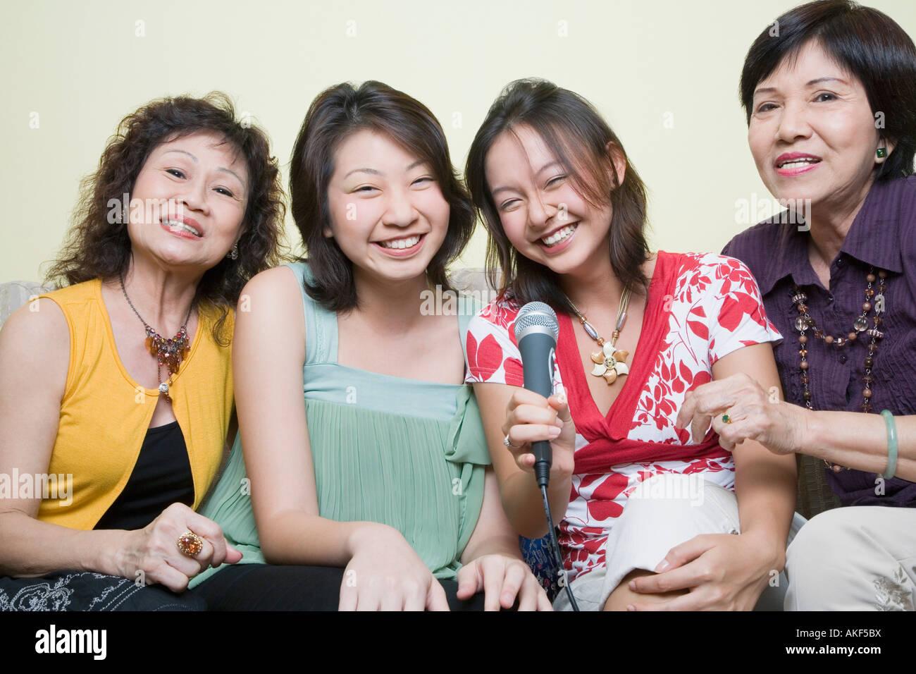 Deux jeunes femmes chantant avec leurs grands-mères dans les microphones Photo Stock