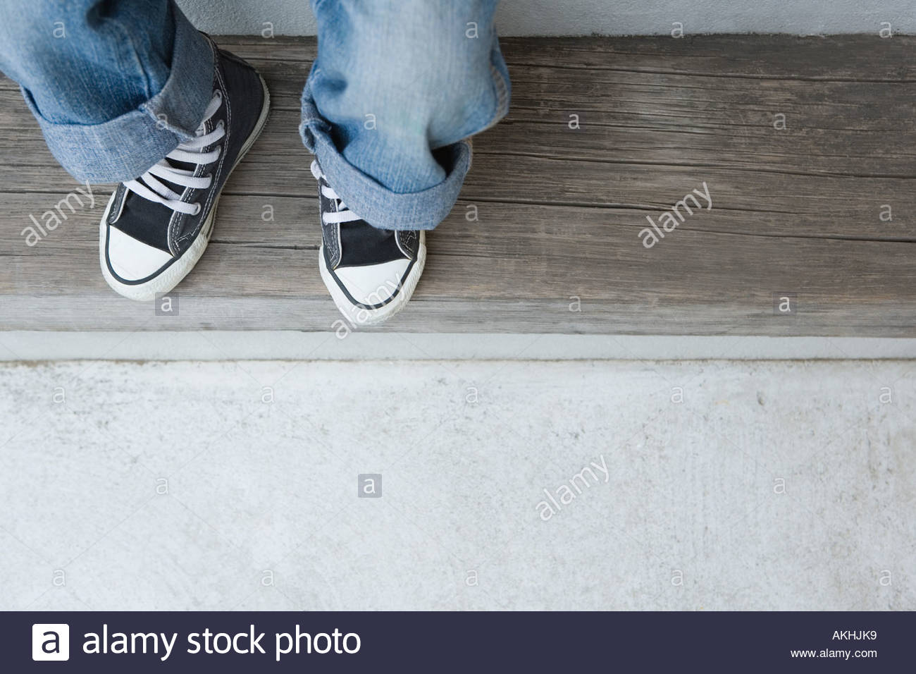 Un enfant portant des jeans et des formateurs Photo Stock