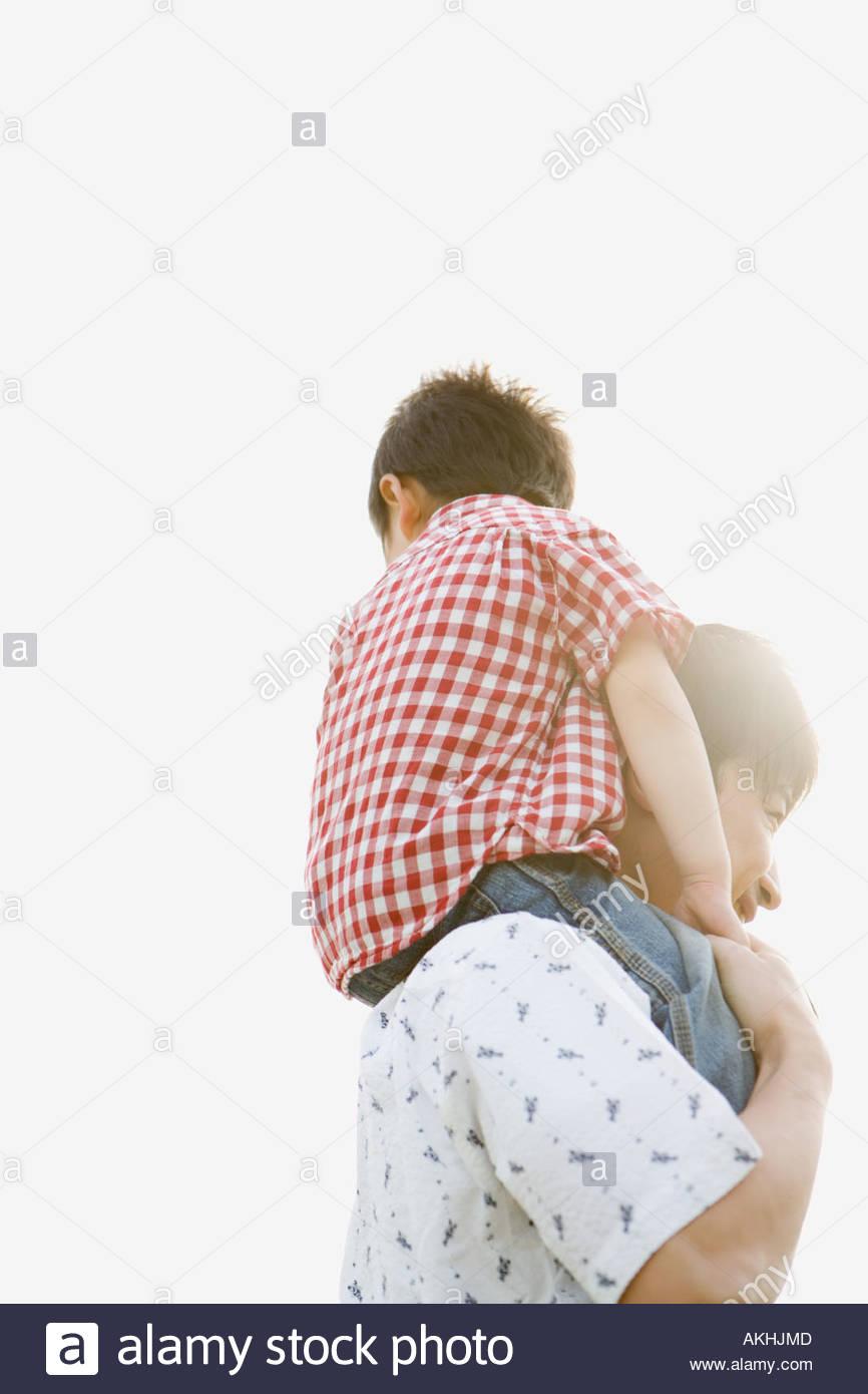 Père épaule, … son fils Photo Stock