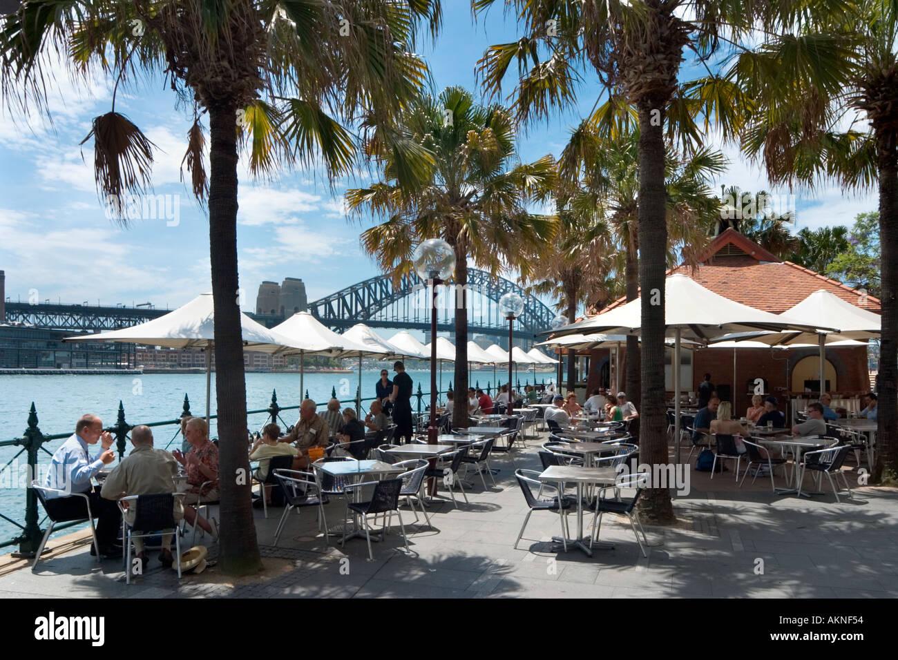 Cafe de la chaussée à Circular Quay avec le Harbour Bridge derrière, Sydney, New South Wales, Australia Photo Stock