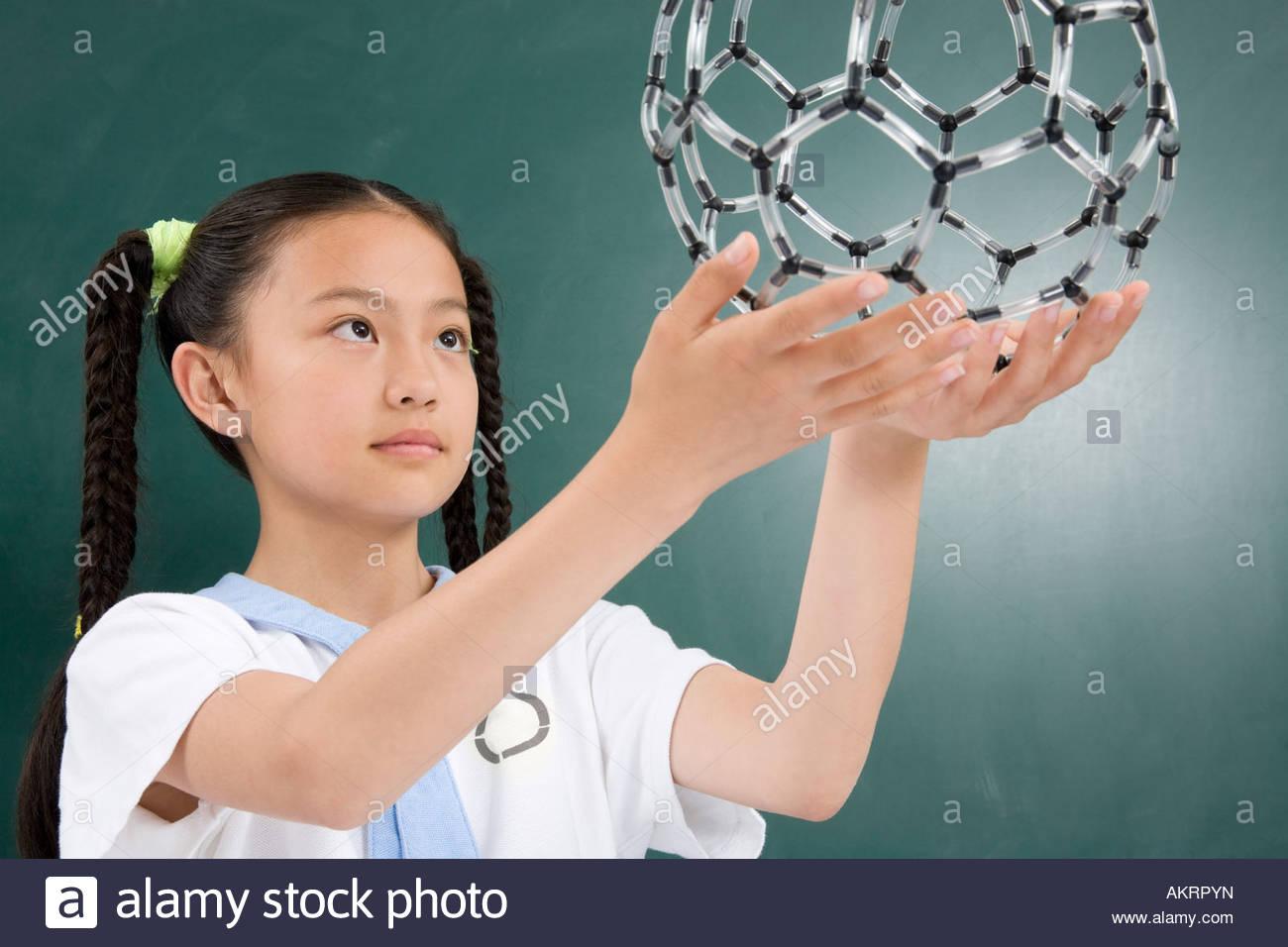 Une jeune fille tenant un modèle scientifique Photo Stock