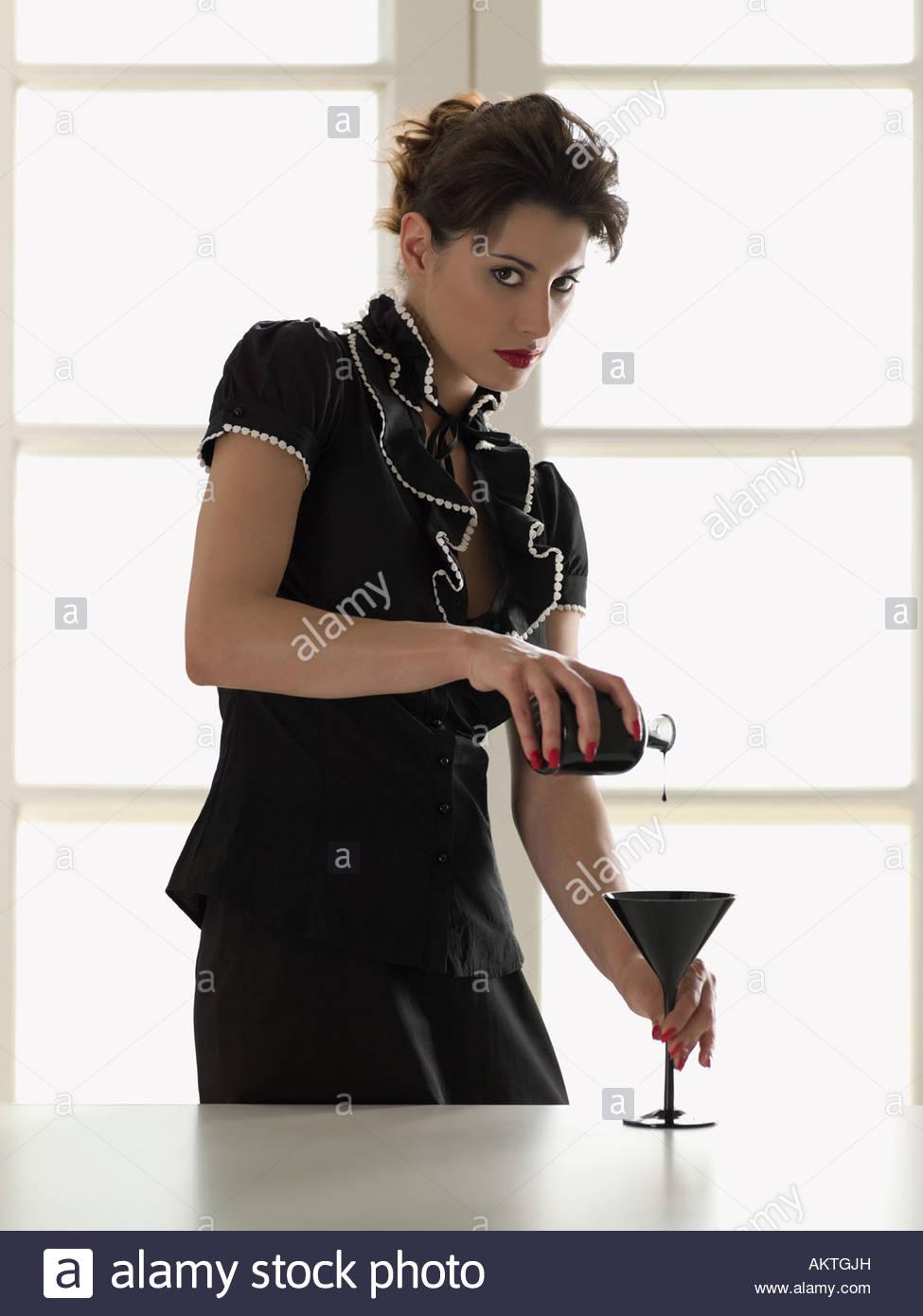 Sinister woman pouring un verre Photo Stock