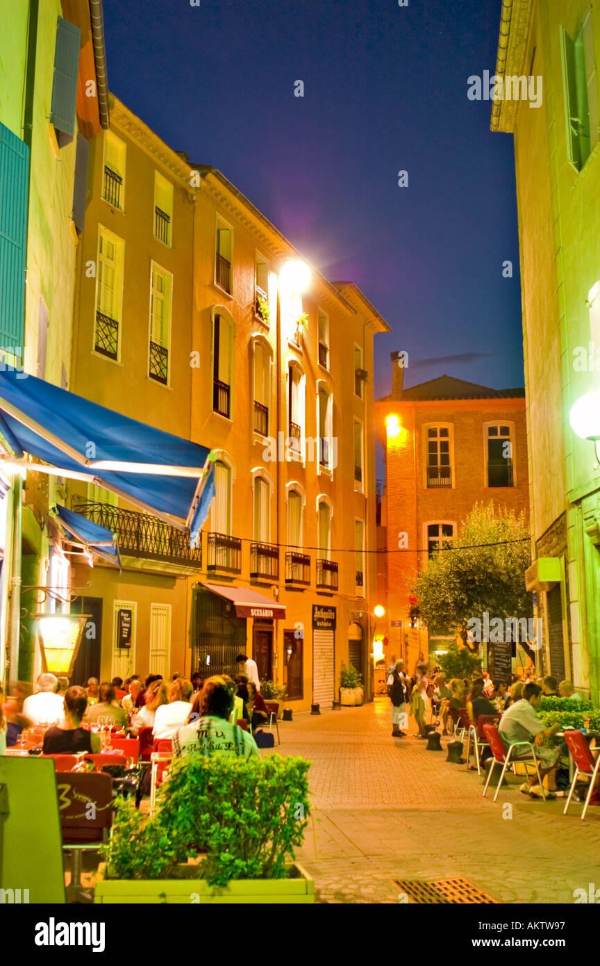 Restaurant français terrasses bondées, scène de rue piétonne Perpignan Sud de la France dans le vieux centre ville, lampadaires la nuit Photo Stock