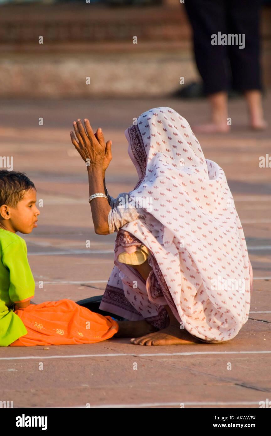 Une grand-mère musulmane sites avec ses petits-fils dans la cour de la grande mosquée Jama Masjid dans Photo Stock