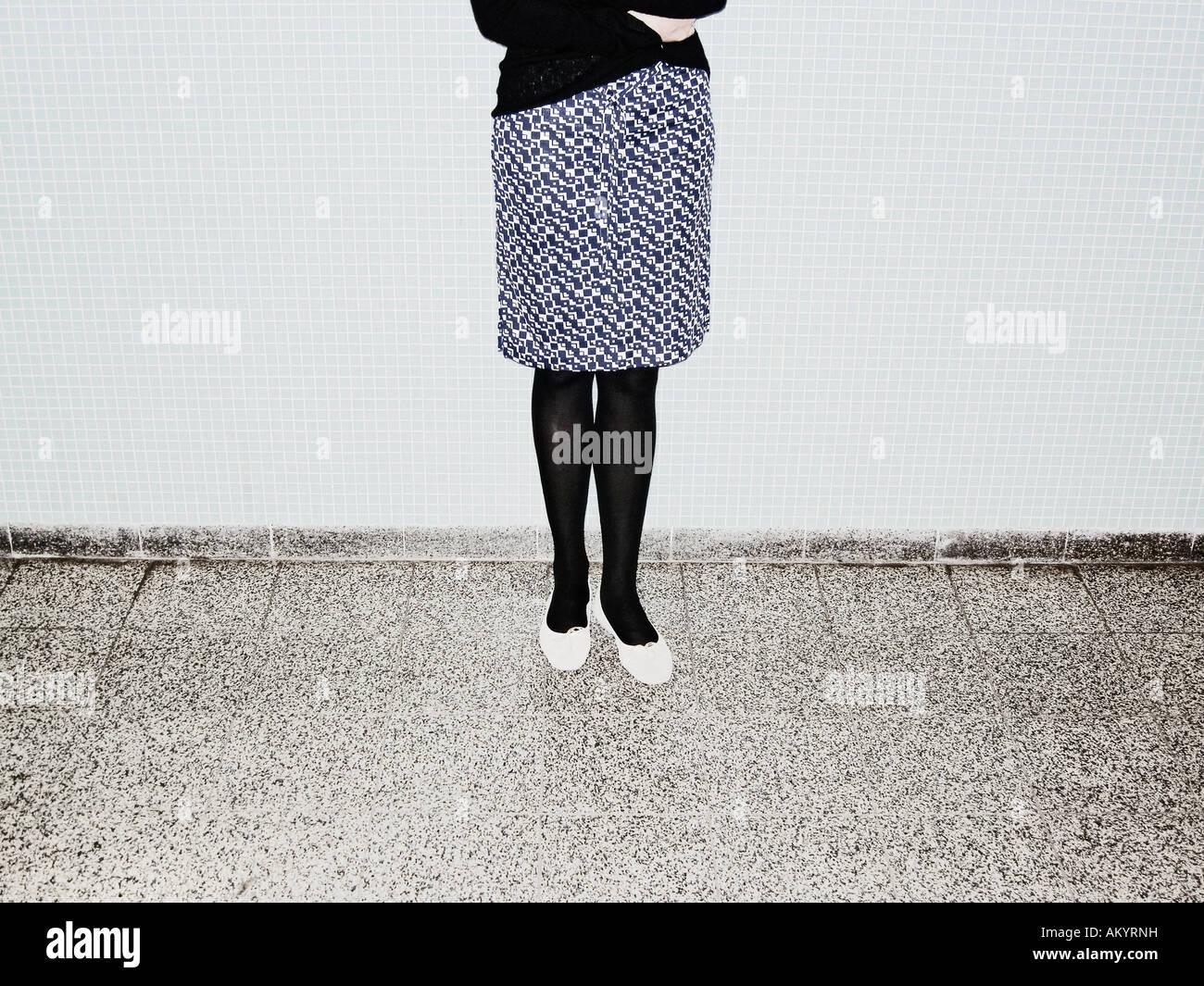 Jeune femme avec Jupe à carreaux debout devant des murs de carreaux bleus Berlin Allemagne Photo Stock