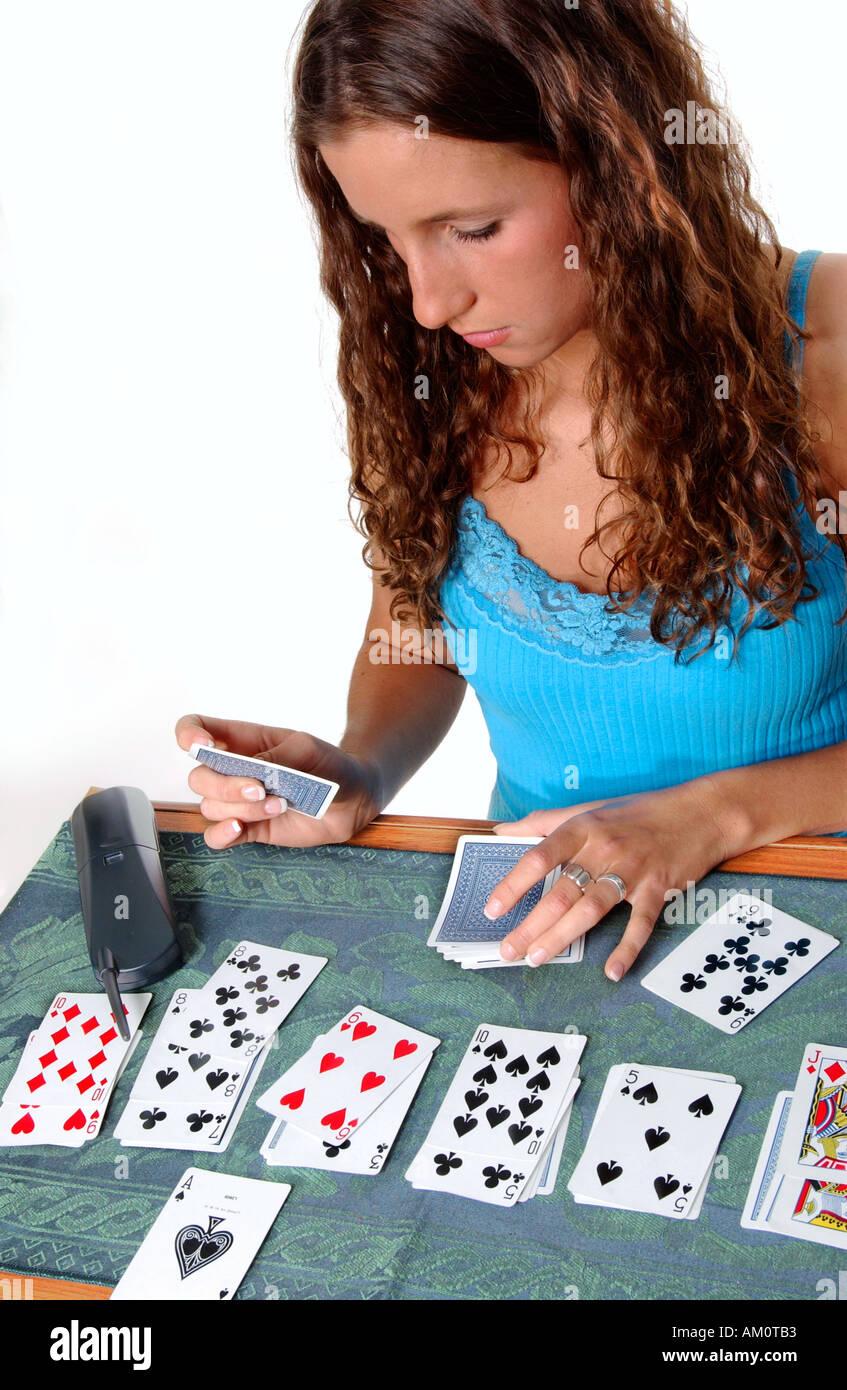 Caucasian Girl joue Solitaire et attend l'ami d'appeler, USA Photo Stock