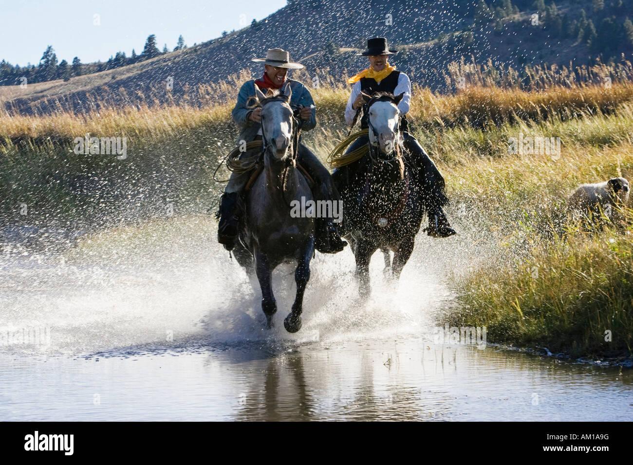 Cowboys équitation dans l'eau, wildwest, Oregon, USA Banque D'Images