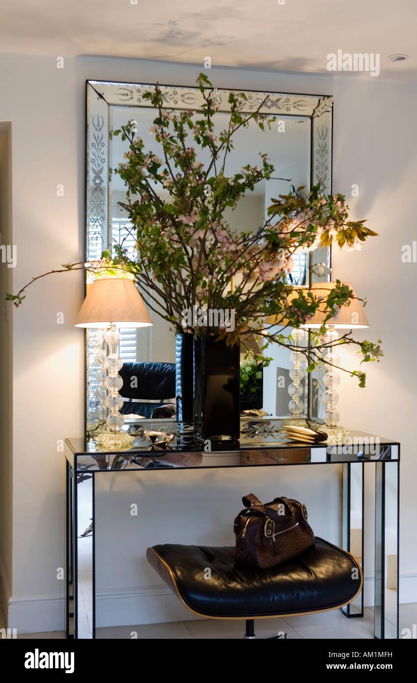 Composition florale sur table en miroir avec siège en cuir Photo Stock