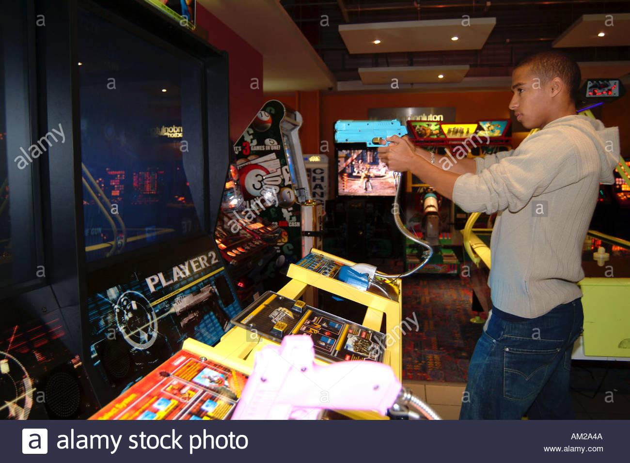 17 Ans Adolescent Jouer Jeu De Tir En Salle De Jeux Electroniques Uk Photo Stock Alamy
