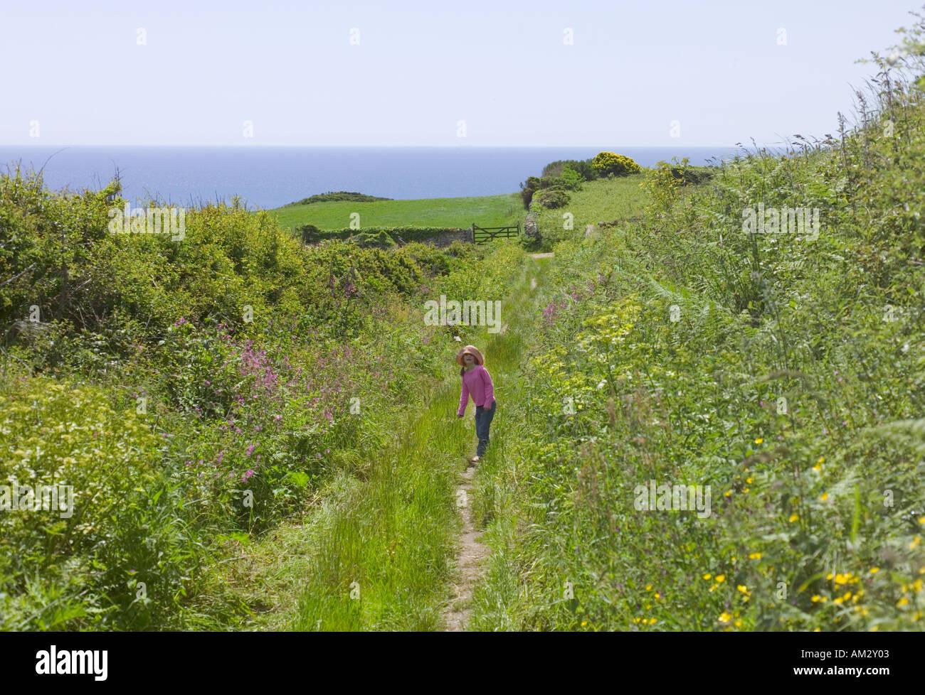 Chemin de campagne dans le sud du Devon UK Young gril en revenant sur la mer derrière la caméra Photo Stock